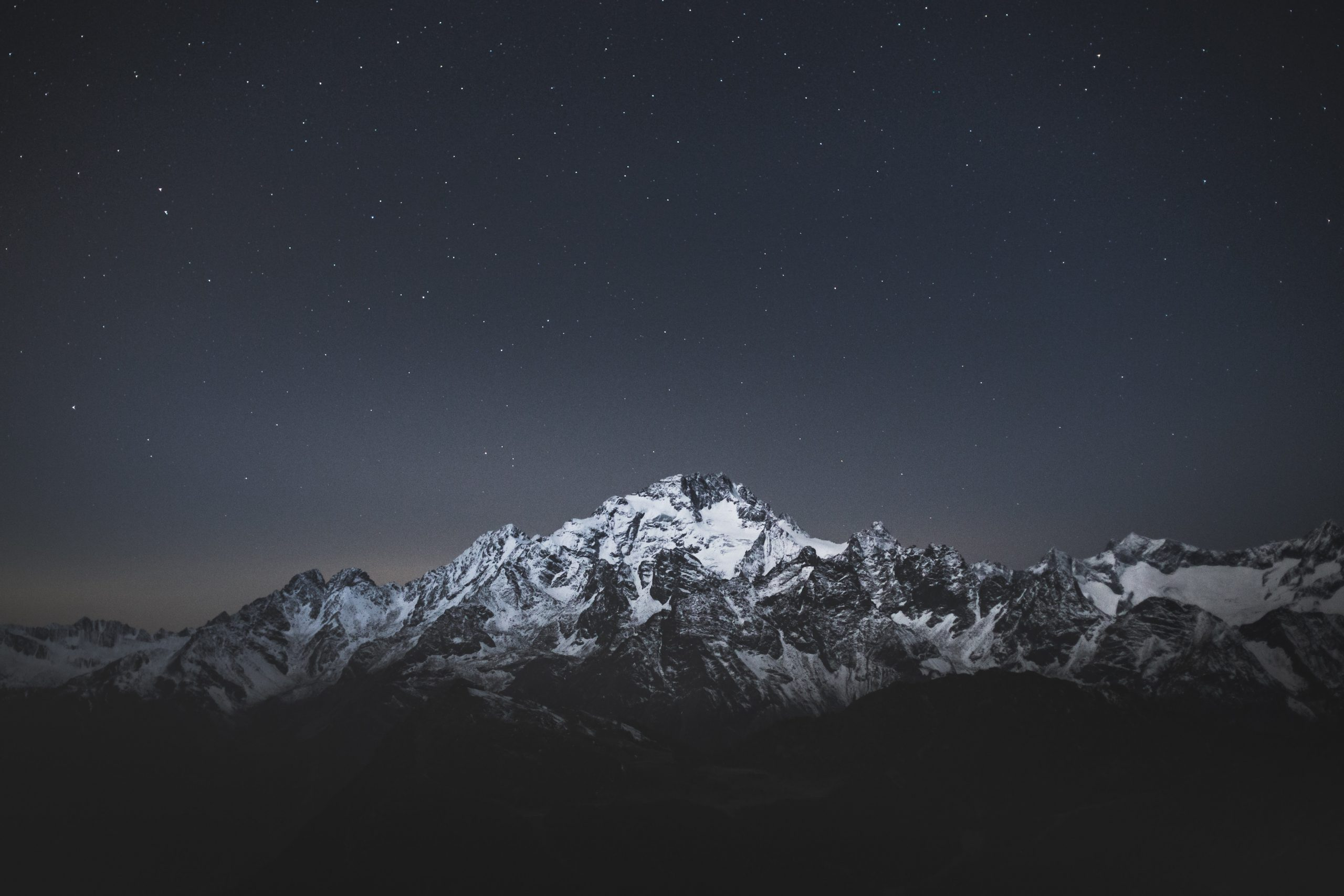 snow covered mountain under blue sky during night time