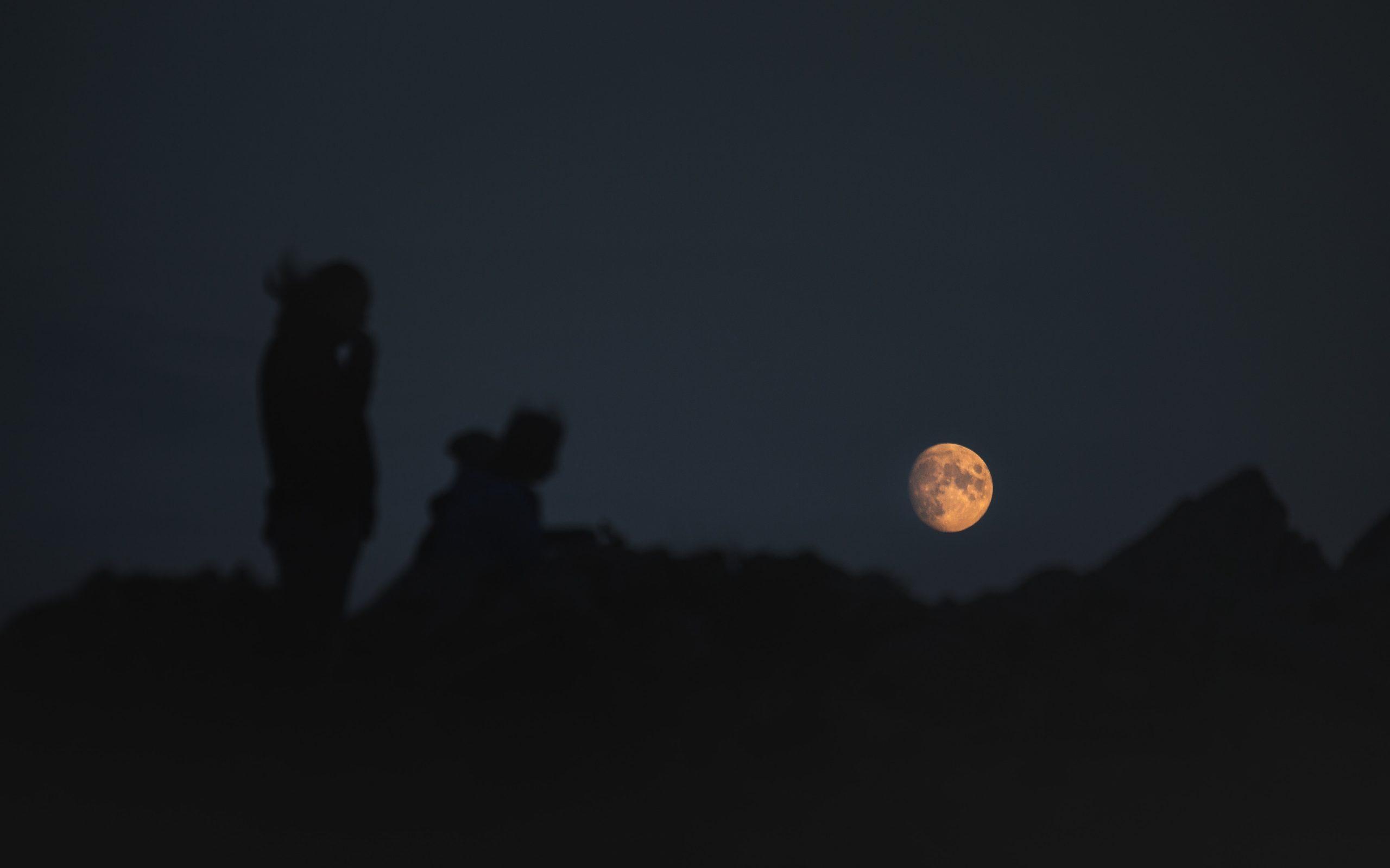hikers looking at moonrise at night