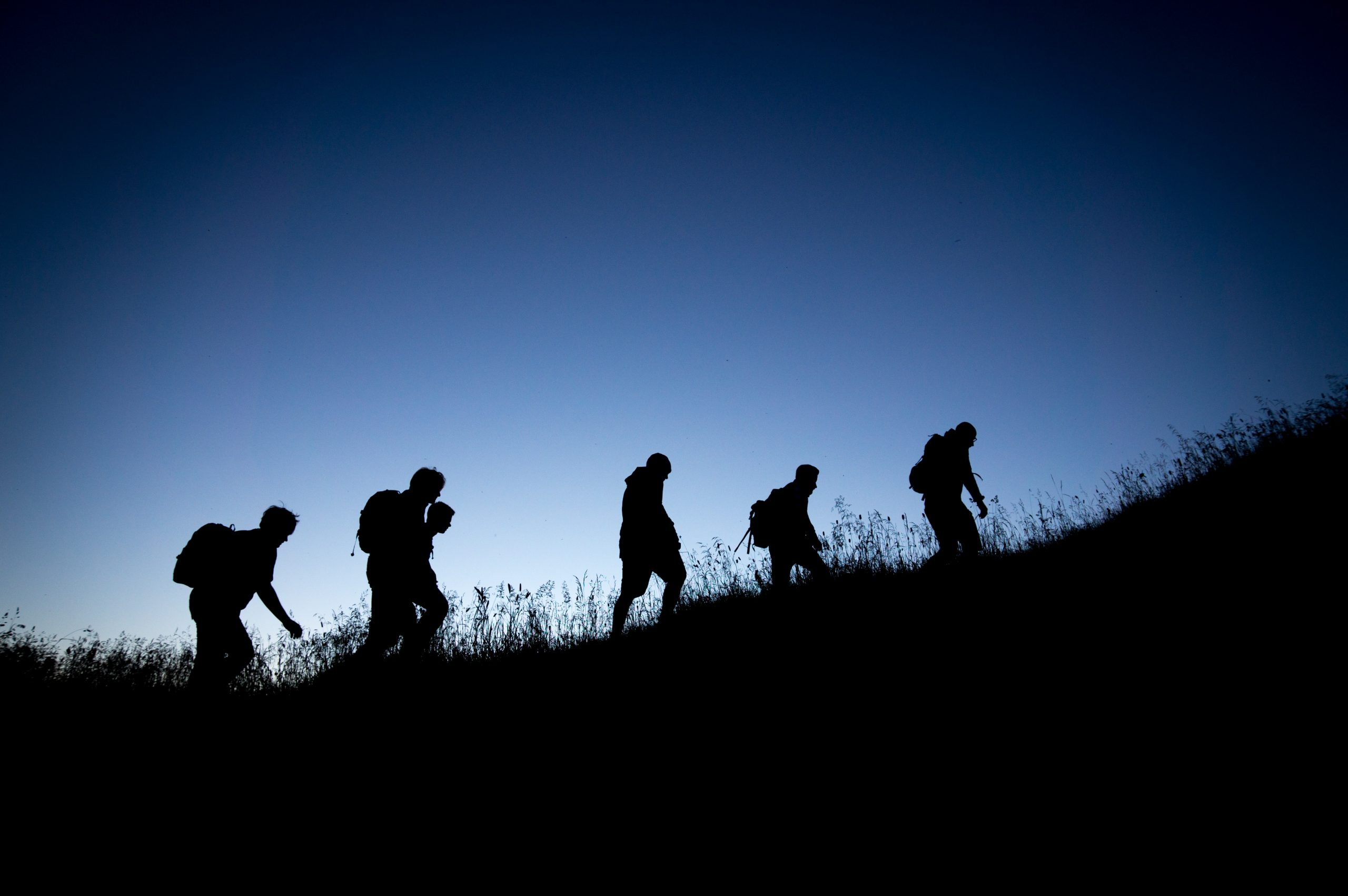 silhouette of people hiking at night
